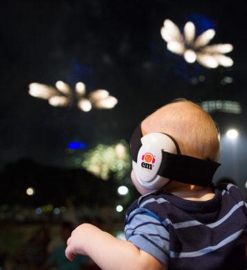 bébé portant des coquilles insonorisantes sur fond de feux d'artifices