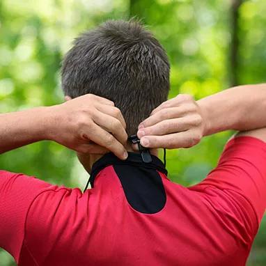 homme qui installe un fil qui relie ses appareils auditifs et qui s'accroche à son collet de chandail